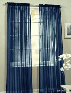 navy blue curtains maybe layered with a thicker tan on the ends for the living room coordinating with the blue in the rug