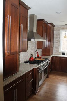 Contemporary Medium Colored Shaker Style Cabinetry, White Granite Countertop, Subway-Style Tile Backsplash, and Stainless Steel Range and Range Hood.