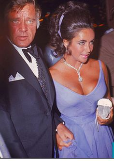 """Our girl, Elizabeth Taylor with Richard Burton in tow at the 1970 Oscars.  A stunning Red Carpet ensemble that was the essence of simplicity-a relatively unadorned violet dress to go with Elizabeth's eyes, some jewelry (diamonds, of course), and just enough cleavage to ever-so-slightly push the boundaries of good taste.  For a better view of that diamond, see """"Jewelry""""."""