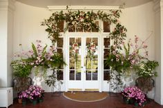 Fresh dogwood and cherry blossom branches help frame the reception entrance. Aisle markers and a swag from the ceremony were re-fashioned for this event!