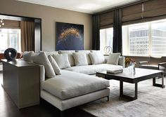 This Ritz-Carlton Showcase apartment designed by Doug  Atherly exemplifies a naturally clean, Zen-like space high above the streets of  Chicago. In the contemporary living room, a low L-shaped sofa from Minotti  establishes the seating area, which is surrounded by a wrap-around sofa cabinet  to keep the simple space clutter-free.