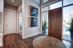 Beautiful entry from the Cantata Showhome featuring Lauzon's Smokey Grey Hard Maple hardwood flooring from the Essential Collection. Project realized by Baywest Homes in the Rocky View County (Springbank) Harmony collection. @baywesthomes
