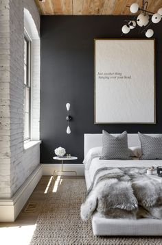 Contemporary bedroom with black accent wall, exposed whitewashed brick, and natural elements like jute rug and fur throw.