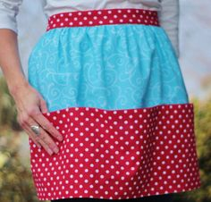 Gathered half apron in 100% cotton. Main panel is aqua blue with swirl pattern; waistband, ties and pocket panel are deep red with white polka dots. Features three large utility pockets that make it perfect for kitchen, garden, craft and general home use. Inspired by my Scandinavian heritage.  Front panel is approximately 18 wide at waistband, 30 wide at bottom and 17.5 long. Ties are each 30 long, from the edges of front panel.  This apron is sewn and ready to ship!  Made with love in a…
