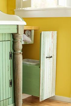 Decorative reclaimed porch posts under this wall-hung sink suggest freestanding furniture. The trash-bin pullout, with a cubby for bags, was made using reclaimed tongue-and-groove boards and a home-center screen-door pull.