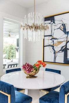 Brass and lucite chandelier brings elegance to a blue and white dining room boasting luxurious furnishings such as a round white dining table with gold and blue sapphire velvet chairs. Blue Dinning Room, Blue Velvet Dining Chairs, Dining Room Design, White Round Dining Table, Round Dining Room Sets, Contemporary Dining Room Lighting, Contemporary Decor, Modern Decor, Contemporary Kitchens