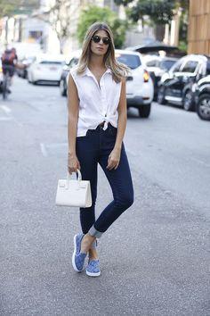 Blusa branca com nó na cintura, calça skinny azul escuro, tênis azul