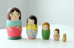 Munieca's Nesting Dolls  -  These charming wooden nesting dolls were painted by me. I used acrylics, vintage paper & Japanese paper.  These little sisters love each other as well as their pet.  Note that the little one it's an adorable kitty.  85.00, via Etsy.