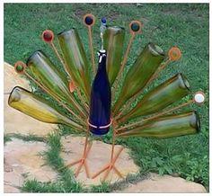 Pavão decorativo para jardins feito com garrafas de vidro coloridas.