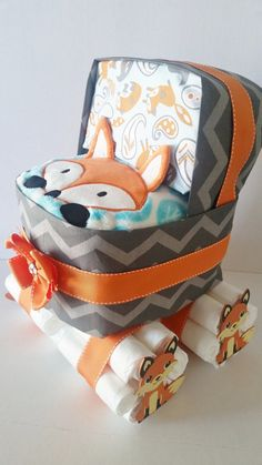 A baby carriage or diaper stroller cake will be the perfect addition or centerpiece to a baby boy shower. The foxes compliment a woodland animal or fall/winter themed baby shower. This diaper cake is adorned with gray chevron and fox fabric with orange grosgrain ribbon as well as