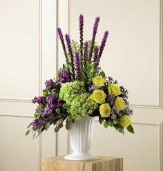 <p>Contrasting blooms of purple, green and yellow create an original and beautiful expression of sympathy and sorrow, eminently appropriate for celebrating a life that has passed. This stately arrangement handcrafted by a local The Flower Factory artisan florist features an eye catching silhouette of purple liatris stretching heavenward surrounded by yellow roses, purple stock, lavender Monte Casinos and green hydrangea and button poms in a pedestal urn with the look of fine white ceramic…