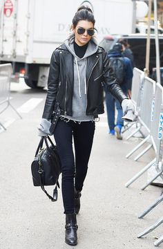 Kendall Jenner wears a hoodie, leather jacket, skinny jeans, ankle boots, and a duffle bag