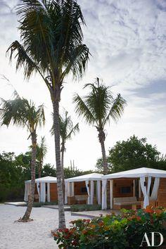 Sunbrella-fabric cabana tents are arranged along the beach area adjacent to the sand-bottom pool.