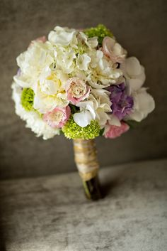 White wedding bouquet with pink, green and purple accents - photograph by Erik Hornung.