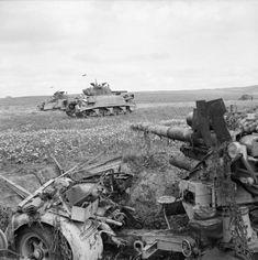 Sherman tanks advance past a knocked-out 88mm anti-tank gun, 23 April 1943.