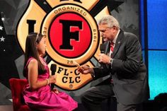 IAFF General President Schaitberger presents a final check to MDA National Goodwill Ambassador Abbey Umali during the MDA Telethon broadcast from Las Vegas over the Labor Day Weekend. IAFF affiliates conducted Fill-the-Boot campaigns across the country.