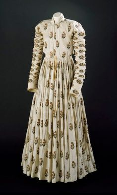 Man's robe of white cotton, with repeating staggered pattern of embroidered floral motifs in gold-wrapped thread and floss silk. Long sleeves, front opening, floor-length gathered skirt – 18th century, India.