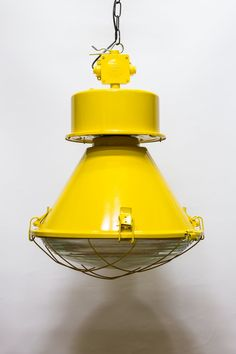 Very large and tasty popping pendant , suckers for appealing industrial design. This old lamp is cleaned and then repainted in a bright yellow color. A metal frame at the bottom with a solid glass shade .