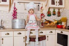 Kleines Mädchen in Schürze und Mütze des Kochs in der Küche sitzen im Haus. Helfer Mutter. 2 Jahre alt.