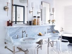 Elegant black and white bathroom with double sink; claw-foot tub