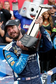 Martin Truex Jr, driver of the #78 Auto-Owners Insurance Toyota, celebrates with the trophy in Victory Lane after winning the Monster Energy NASCAR Cup Series Bank of America 500 at Charlotte Motor Speedway on October 8, 2017 in Charlotte, North Carolina.