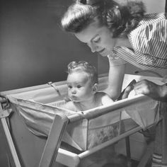 Mother bathing baby in a bathinette, circa 1950's.