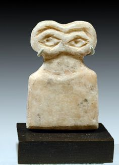 """Tel Brak, modern day Syria, Middle Uruk Period, ca. 3700 to 3500 BCE. This is an abstract carved stone figure with flat body surmounted by two well defined incised eyes. These idols were used for dedication to an all seeing god who watched over the populations of early Mesopotamia. They have been excavated from a building we call the Eye Temple; many are incised with multiple sets of eyes and other have """"children"""" -- smaller eyes and body carved on the body of the larger idol. Wide eyes…"""