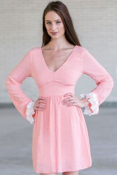 This beautiful shade of pink is so feminine! We love the contrasting applique lace trim on the long bell sleeves. The Pink Bubblegum Bell Sleeve Dress is fully lined. It is made of a flowy lightweight material that is girly and romantic. It has long bell sleeves V shaped neckline, A-Line flowy cut. The tie string back ties the open keyhole back. A hidden back zipper completes the dress. This dress is feminine, romantic and boho chic. This dress can be dressed up with pretty jewelry and…
