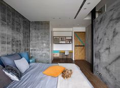 An industrial bedroom with concrete walls, wood floors and gray bedding