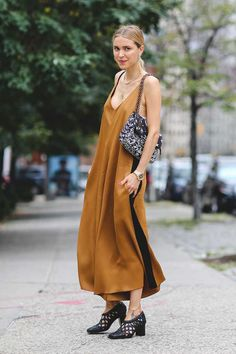 ELLE loves... this street style look from New York Fashion Week Spring/Summer 2015.   Pernille Telsbael pairs a loose-fit, brown, strappy maxi dress with a black and white printed handbag and Celine shoes.   Minimal gold jewellery and a pony-tail help make this look chic and wearable!