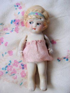 This adorable bisque doll still wears her original little pink dress