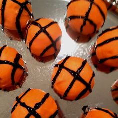 Donut holes covers in chocolate died orange decorated in black piping gel made to look like basketballs cute idea for march madness