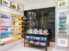 PALAU pharmacy  Barcelona – Spain with the yellow LED lighting, by the copper strongboxes with their centuries-old coats of arms. An old iron cabinet serves as the backdrop for creating window displays.