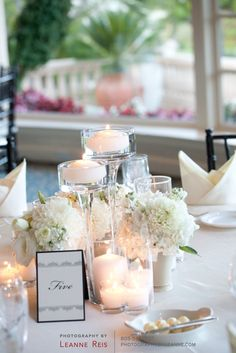 Mixture of small flower arrangements with votives
