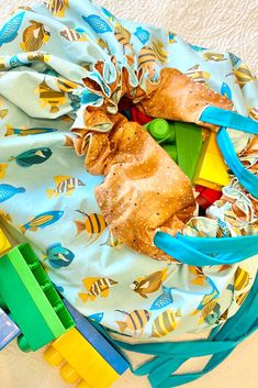 Fun drawstring play mat that converts to toy bag for fun at home or on the go   Fun fish design with bold colors in aqua, teal and golden yellow  Easy to use, durable and washable for boys and girls of all ages Toddler Boy Gifts, Toy Storage Bags, Fabulous Birthday, Fish Design, Kids House, Legos, Fabric Patterns, Boy Or Girl, Dinosaur Stuffed Animal