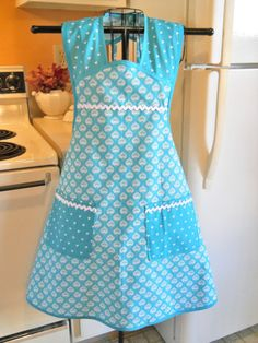 This is a very old fashioned looking vintage style full apron. The white floral tear dropped shapes are on a aqua teal background is contrasted with white triangle shapes on the same colored background. Its then finished with teal bias and white rick rack. This is only available