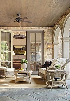 Gorgeous outdoor space ~ stonework, arches, stained ceiling, and classic wicker from frontgate.com