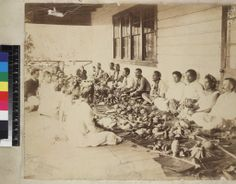 """""""Samoan Feast"""". View of men and women seated on verandah floor with food laid out. Fanny Stevenson, wife of Robert Louis Stevenson, is seated at the far end. One of a set of mounted prints from Rev. William Huckett. Stamped A J Tattersall. Tattersall was resident in Samoa from 1886 to 1951. He sold the business in 1949, but all original negatives were destroyed in the Samoan hurricane of 1966."""