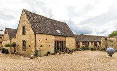 This Cotswold barn conversion has turned a selection of derelict farm buildings into a family home perfect for entertaining Garage Exterior, Boundary Walls, Stone Barns, Courtyard House, Carriage House, Types Of Houses, Building A House, Home And Family, Cabin