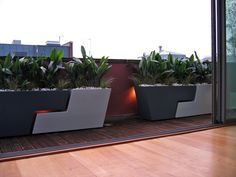 3 pairs of interlocking planters in contrasting slate and agate colours line the red walls of this long terrace. Aspidistra and Acorus give lush planting while low voltage #contemporary #garden #lighting #design adds ambience behind the planters.