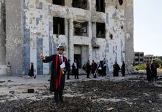 A new graduate of Benghazi University takes a selfie in front of a ruined building at his university's former headquarters, which was destroyed during clashes in 2014. Esam Al-fetori / Reuters
