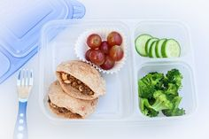 Overhead photograph consisting of mini pital pockets, steamed broccoli, grapes, and cucumbers.