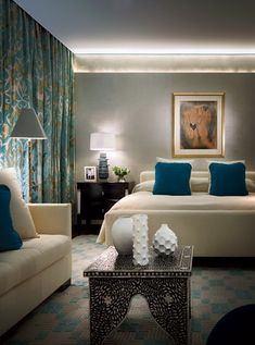 Bedroom - Defused lighting add softness & romance.  The colour palette of turquoise, gray and soft white are both calming and restful.  Cleverly selection decor items/furnishings.  Very elegant.