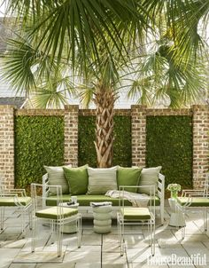 In the interior courtyard, fig ivy softens a brick wall and the addition of a mature palmetto tree adds a sense of permanence. The West Elm sofa is covered in a Sunbrella fabric. Click through for more photos of this southern home by designer Michelle Prentice in Beaufort, South Carolina.