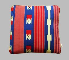 Cushion Red Arrow is a square cushion that comes with removable cover and interior duck feather cushion pad. The mix of bright red, blue and cream create an air of summer to the room. Made of 100% cotton, this is African wax fabric.  Dimensions: 50cmx50cm.