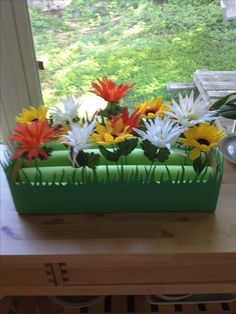 """Flower garden sensory box. Cardboard box with pool noodles cut in half. Kids can """"plant"""" fake flowers between the rows."""