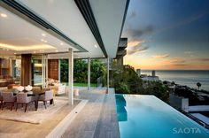 Bold contemporary lines. Floor planes intersected and connected by vertical timber elements. Mass and void, solid and transparent, open and shut and in and out. Luxury open-plan family living perched above Cape Town, South Africa with views to infinity and the infinity edged pool to relax in and enjoy it all. Who else but SAOTA - Stefan Antoni Olmesdahl Truen Architects.