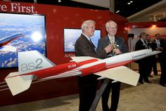 Allan McArtor, chairman and chief executive officer of Airbus Group Inc., left, and Texas billionaire Robert Bass give a toast as they stand with a model of their planned supersonic business jet at the NBAA Business Aviation Convention in Orlando, Florida, on Oct. 21, 2014. (Phelan M. Ebenhack/Bloomberg)