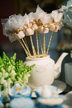 Trufas no palito decorado, envoltas por renda com lacinho de fita dourada.