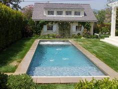 Traditional rectangular pool with water features shooting into the pool and an automatic cover.
